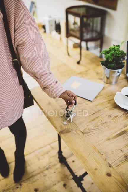 Imagen recortada de afroamericano poner llaves en la mesa - foto de stock