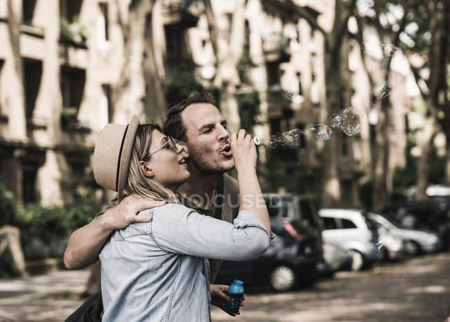 Paar bläst gemeinsam Seifenblasen in der Stadt — Stockfoto