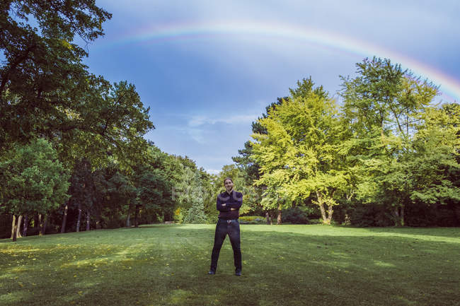 Young businessman standing in park under a rainbow, with arms crossed — Stock Photo