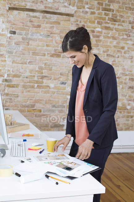 Femme d'affaires souriante regardant des photos au bureau — Photo de stock