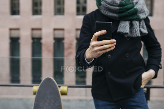 Homme avec téléphone portable et planche à roulettes dans la ville, vue partielle — Photo de stock