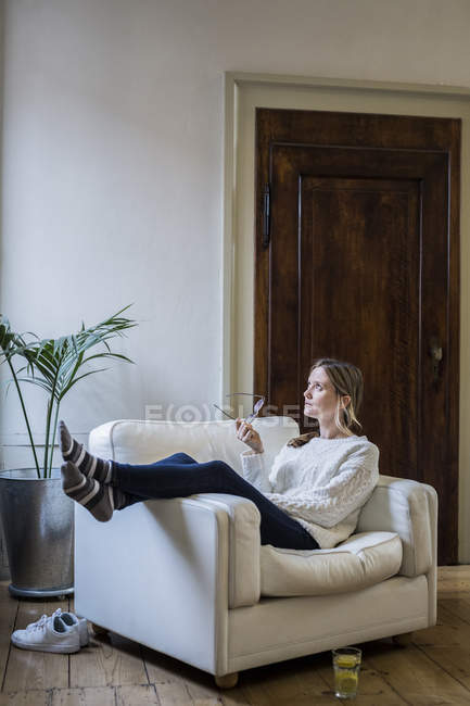 Woman sitting in armchair at home and thinking — Fotografia de Stock