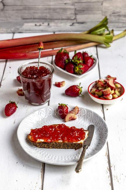 Tavolo da colazione con marmellata di fragole, fragole e rabarbaro — Foto stock