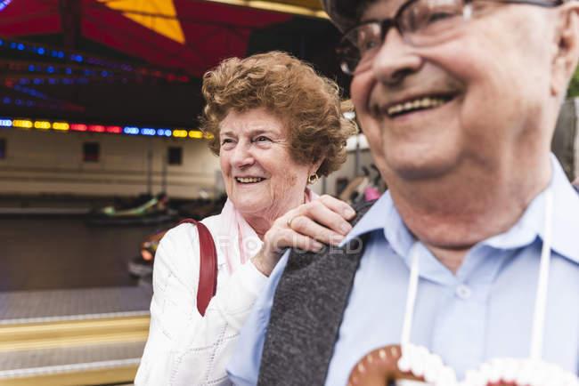 Retrato de mulher idosa se divertindo junto com seu marido na feira — Fotografia de Stock