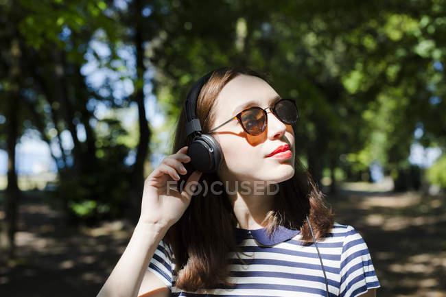 Портрет молодой женщины в солнцезащитных очках, слушающих музыку с наушниками — стоковое фото