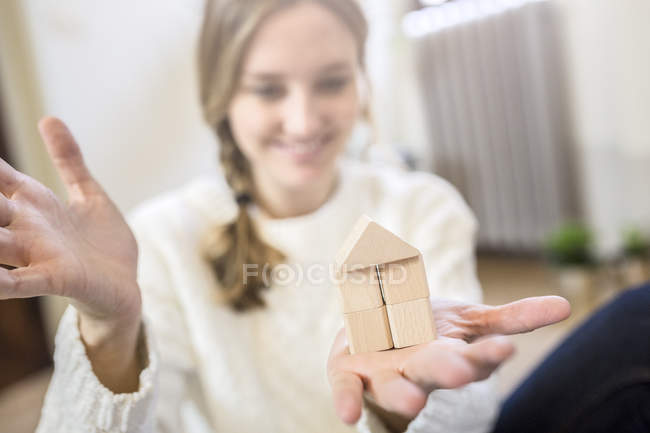 Smiling woman building house with building blocks — Stock Photo