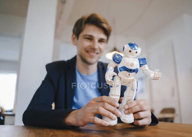Homme souriant tenant un robot — Photo de stock