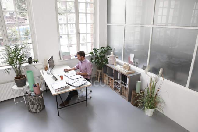 Hombre trabajando en el escritorio en una oficina de loft - foto de stock