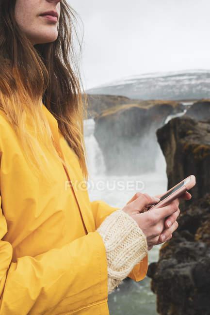Ісландія, жінка з мобільного телефону на водоспад Годафосс — стокове фото