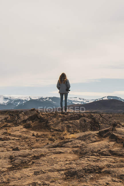 Iceland, female photographer standing on rocks, rear view — Stock Photo