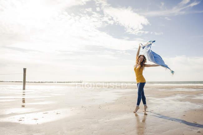 Donna felice divertirsi in spiaggia, ballare e ondeggiare asciugamano — Foto stock
