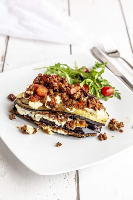 Lasagne d'aubergine sur assiette, rucola et tomate, végétarienne — Photo de stock