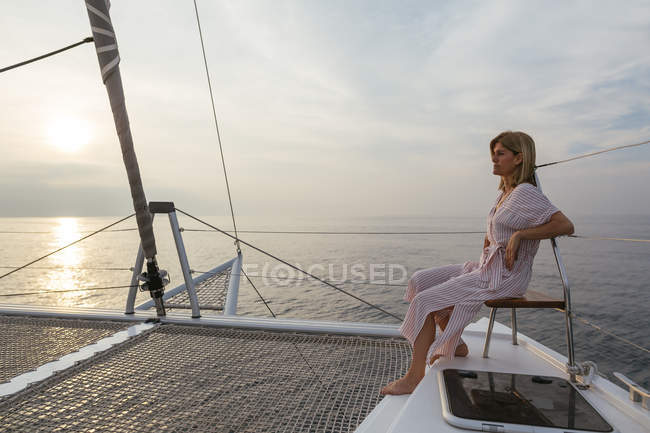 Mature woman on catamaran, watching sunset — Stock Photo