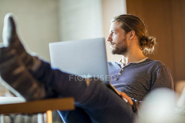 Portrait of pensive young man using laptop — Stock Photo