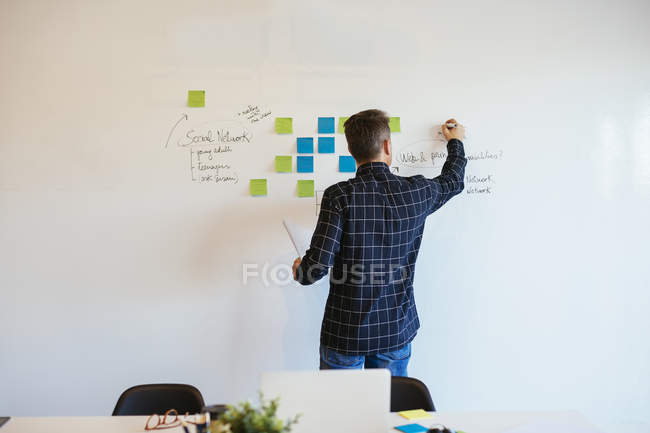 Businessman in office writing on whiteboard — Stock Photo