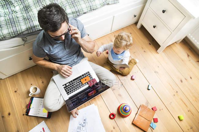 Отец со своим маленьким сыном работает из дома — стоковое фото