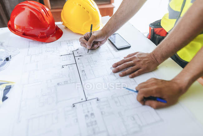 Close-up of workers hands working on construction plan — Stock Photo