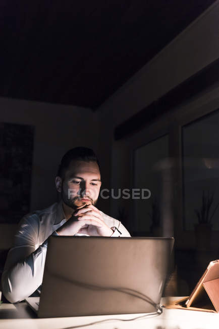 Portrait d'un homme d'affaires assis au bureau la nuit, regardant un ordinateur portable — Photo de stock