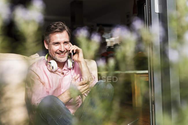 Смолящий зрелый мужчина на телефоне, сидящий у открытой двери террасы — стоковое фото