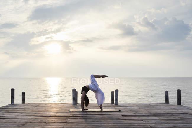 Молодая женщина, практикующая йогу на пристани у моря на закате, urdhva dhanurasana — стоковое фото