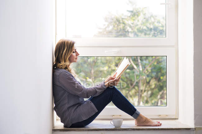 Woman sitting at home on the window sill, reading a book — Stockfoto