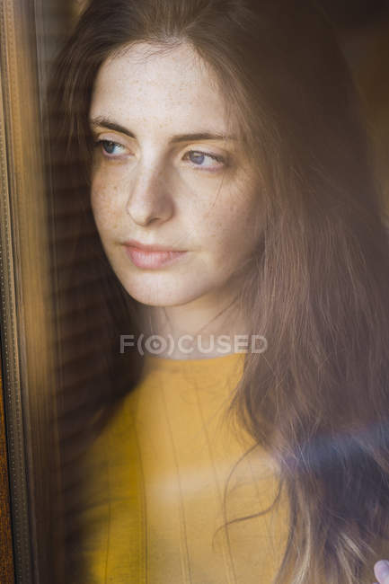Ritratto di giovane donna pensierosa con lunghi capelli castani che guarda fuori dalla finestra — Foto stock