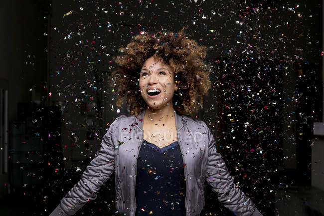 Confetti falling on amazed woman on black background — Stock Photo