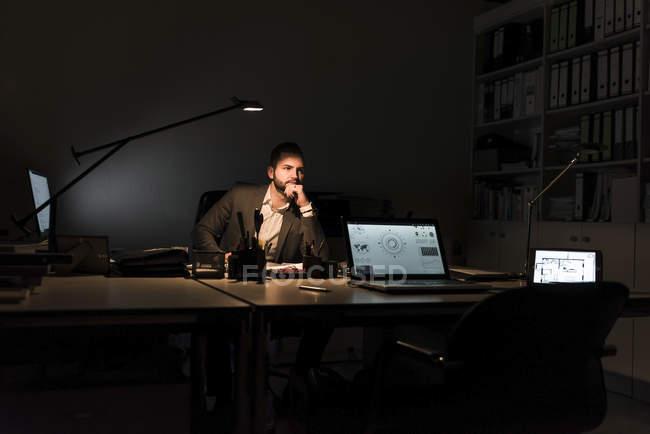 Homme d'affaires pensif assis au bureau la nuit — Photo de stock
