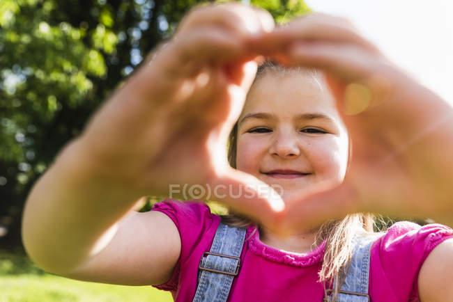 Портрет усміхненої дівчини, яка формує серце руками в парку. — стокове фото