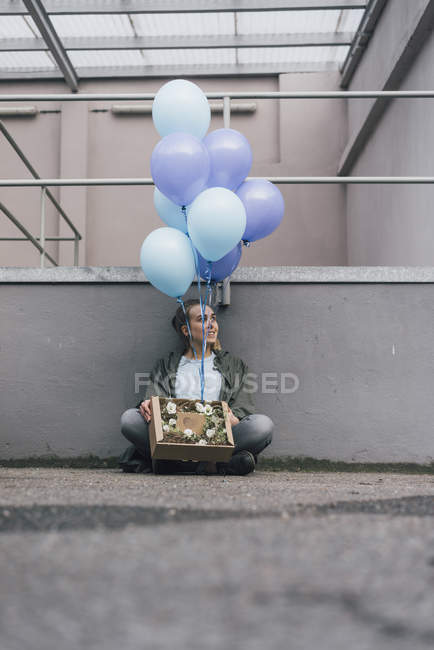 Улыбающаяся женщина с цветами в картонной коробке и кучей синих шариков, сидящих на земле — стоковое фото