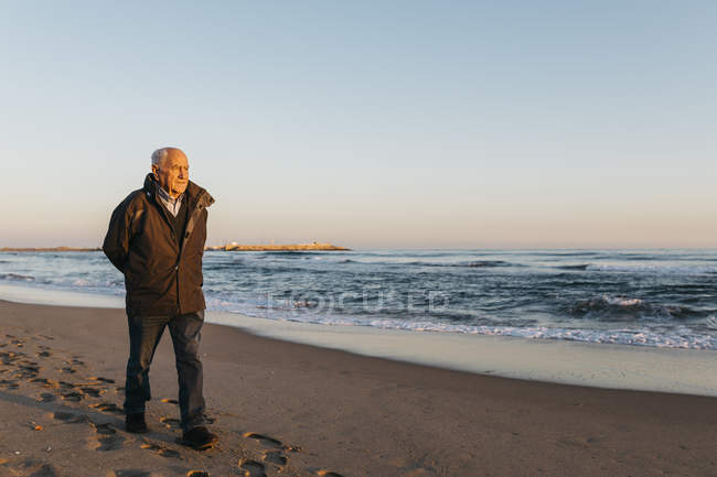 Senior man strolling at beach and looking at sea water and sunset sky — Stock Photo