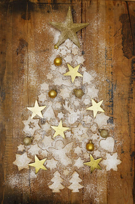 Christmas cookies and golden Christmas baubles and stars forming Christmas Tree on wood — Stockfoto