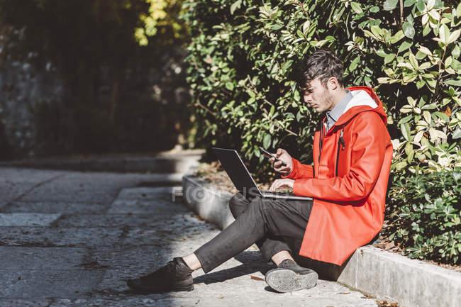 Італія, Верона, турист за допомогою смартфона і ноутбука — стокове фото