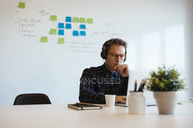 Businessman wearing headphones and using laptop at desk in office — Stock Photo