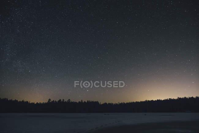 Sweden, Sodermanland, frozen lake Navsjon in winter under starry sky at night — Stock Photo