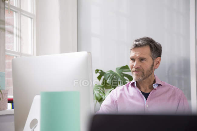 Portrait of a man working at desk in office — Stock Photo