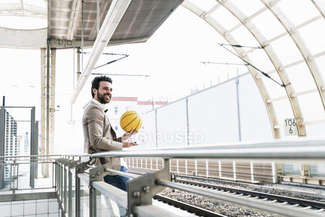 Улыбающийся молодой человек с сотовым телефоном и баскетболом на платформе станции — стоковое фото
