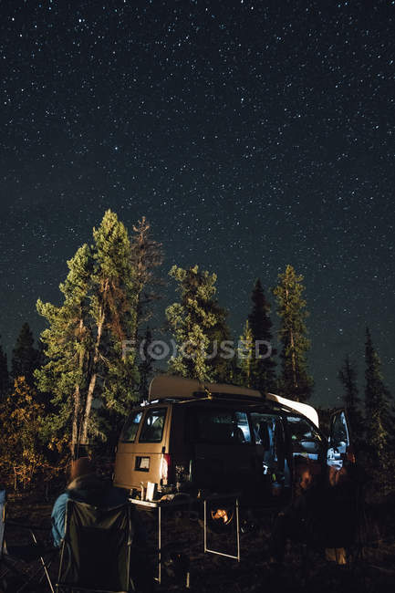 Canada, British Columbia, two men sitting under starry sky at minivan at night — Stock Photo