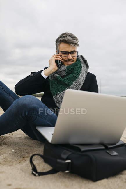 Retrato de hombre de negocios en el teléfono sentado en la playa en invierno y utilizando el ordenador portátil - foto de stock