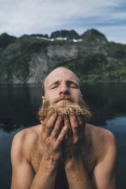 Мужчина моет бороду на озере с закрытыми глазами — стоковое фото