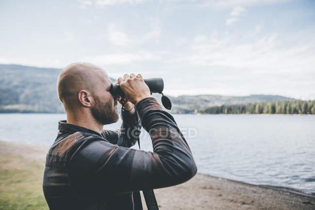 Canada, Colombie-Britannique, homme regardant à travers des jumelles au lac Cultus — Photo de stock