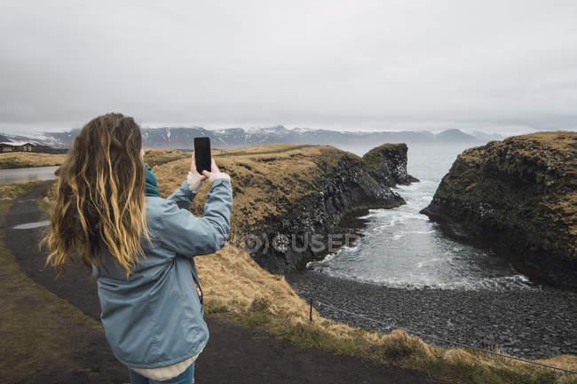 Islande, vue arrière de la jeune femme prenant des photos avec smartphone sur la côte — Photo de stock