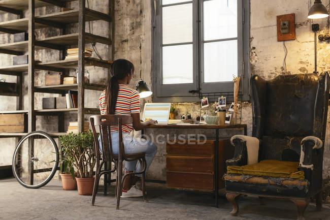 Назад вид молодої жінки сидять на столі в лофт працює на ноутбуці — стокове фото
