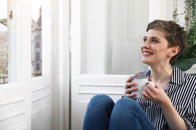 Femme heureuse assise détendue à la fenêtre, buvant du café — Photo de stock