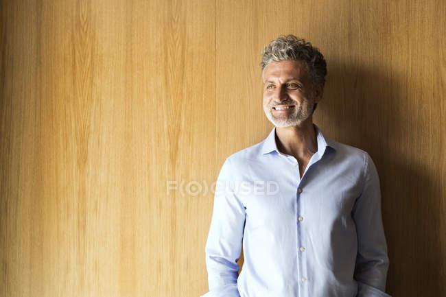 Verticale d'homme d'affaires mûr de sourire se penchant contre le mur en bois — Photo de stock