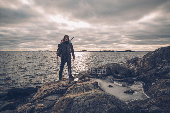 Sweden, Sodermanland, backpacker standing at the seashore under cloudy sky — Stock Photo