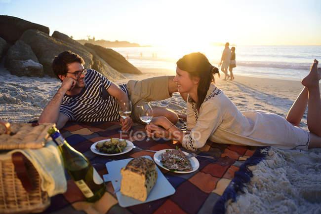 Щаслива пара з пікніка на пляжі на заході сонця — стокове фото