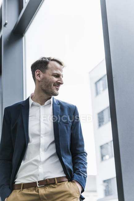 Smiling businessman looking out of window — Stock Photo