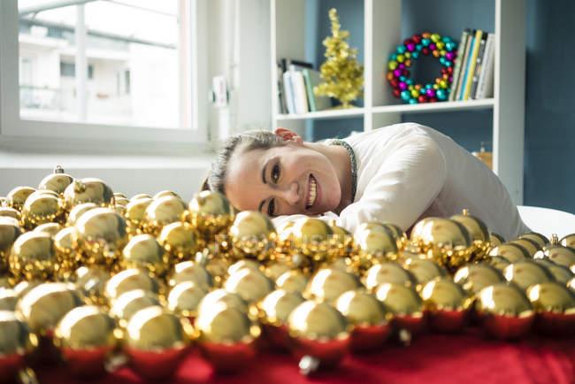 Улыбающаяся женщина сидит за столом со многими золотыми рождественскими безделушками — стоковое фото