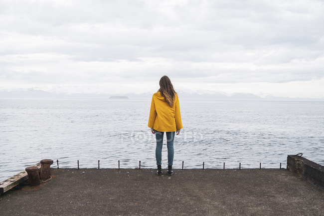 Iceland, woman standing at the sea — Stock Photo